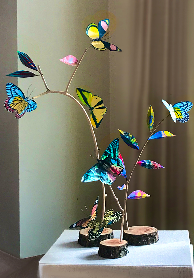 Butterflies made from encaustigraphic material on a sculpture of driftwood.